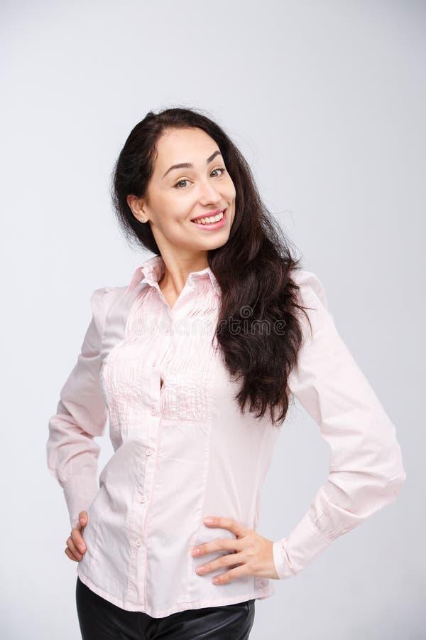 El retrato de una mujer joven con una sonrisa dentuda encantadora, un pelo negro y un marrón observa en un fondo blanco en una ca fotografía de archivo libre de regalías