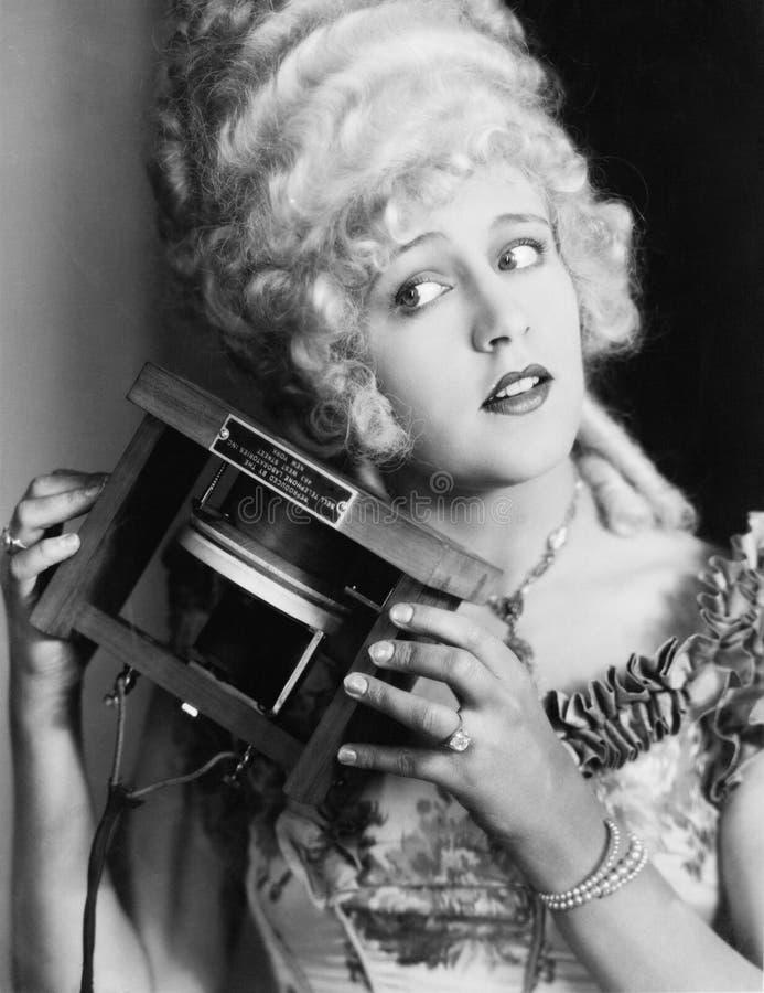 El retrato de una mujer joven que sostiene uno del primer llama por teléfono (todas las personas representadas no son vivas más l fotos de archivo libres de regalías