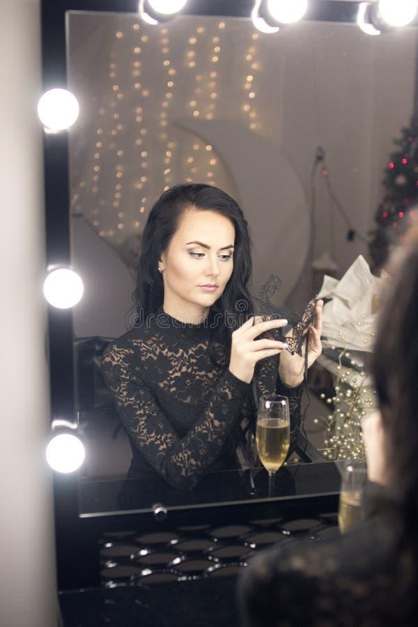 El retrato de una mujer morena joven tiene un espejo grande del maquillaje adentro foto de archivo libre de regalías