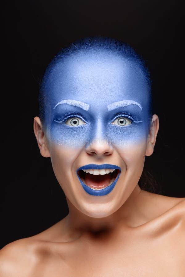 El retrato de una mujer que está presentando cubrió con la pintura azul fotografía de archivo libre de regalías