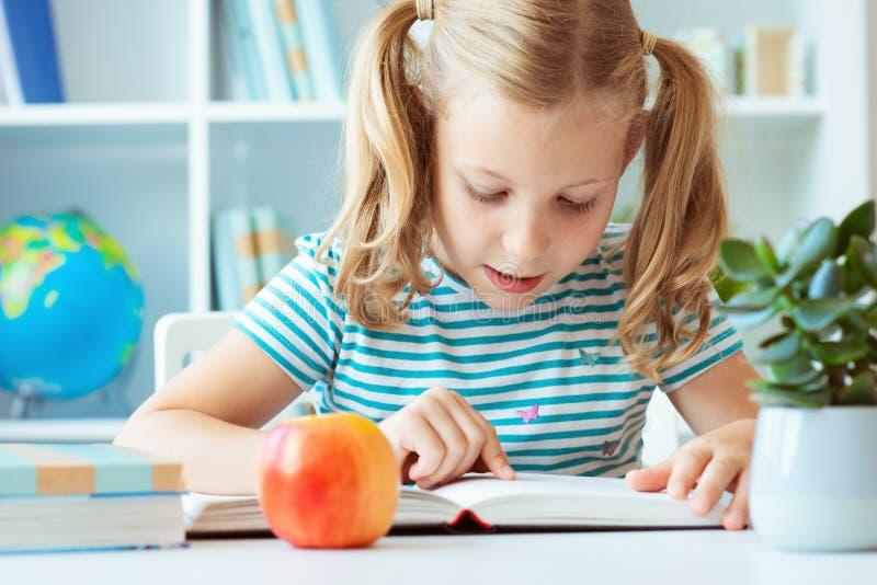 El retrato de una niña linda leyó el libro en la tabla en classro fotos de archivo libres de regalías