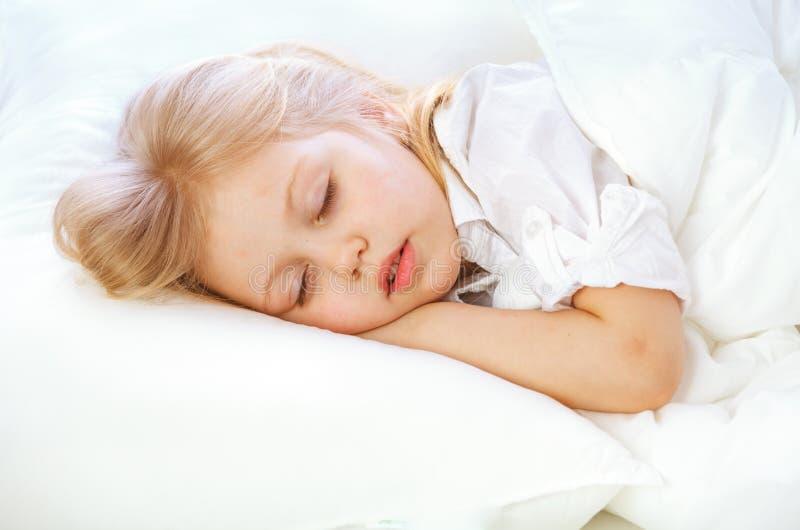 El retrato de una niña se va a la cama, acuesta, duerme, descansa fotos de archivo