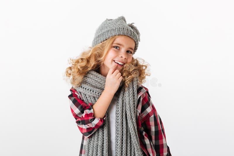 El retrato de una niña sonriente se vistió en sombrero del invierno fotografía de archivo
