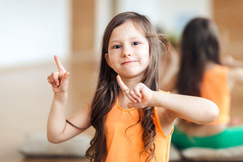 El retrato de una pequeña muchacha feliz en deportes viste, top de la naranja, primer, aptitud para los niños foto de archivo