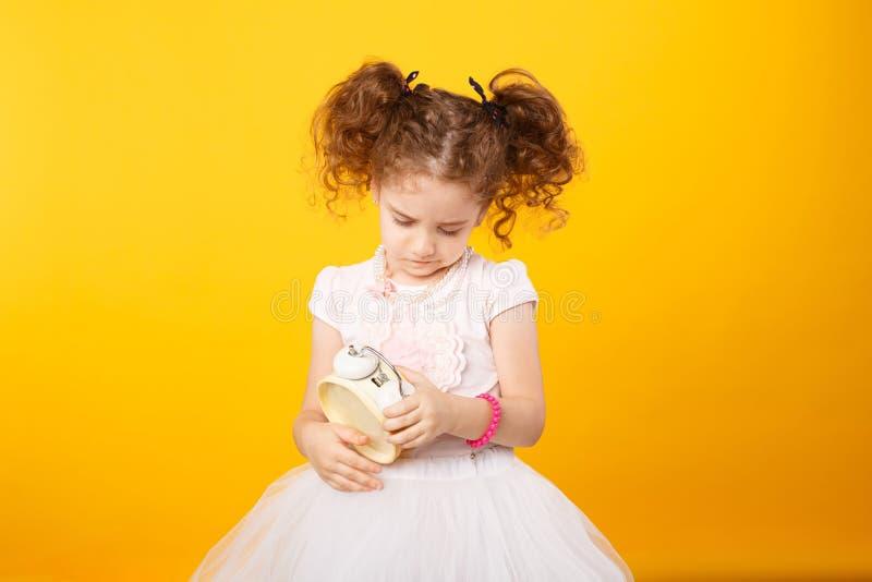 El retrato de una pequeña muchacha rizada adorable, mirando frunció el ceño en un despertador, sobre fondo amarillo Copie el espa imágenes de archivo libres de regalías