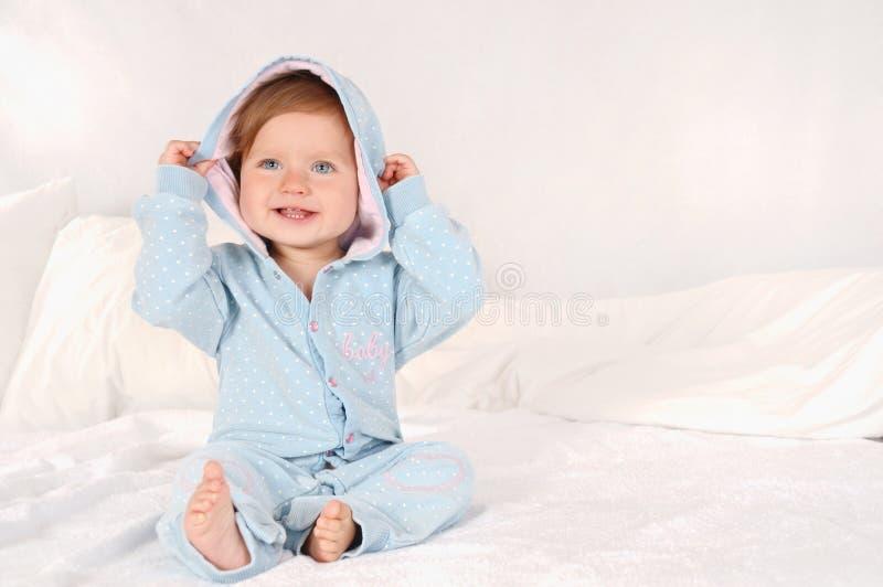 El retrato de una pequeña muchacha sonriente se vistió en pijamas azules en casa imagen de archivo libre de regalías