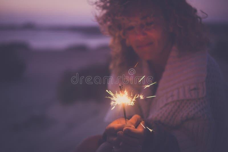 El retrato defocused de la sola mujer atractiva que toma solamente chispea los fuegos artificiales ligeros para celebrar el acont fotos de archivo