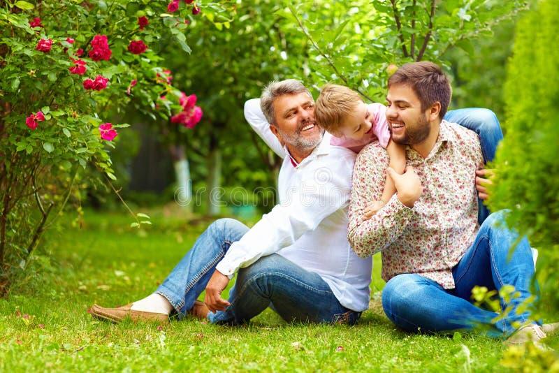 El retrato del abuelo feliz, el padre y el hijo en primavera cultivan un huerto imágenes de archivo libres de regalías