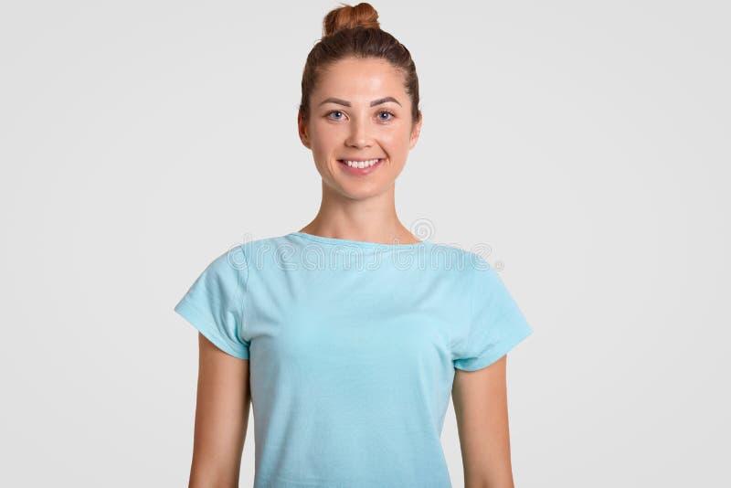 El retrato del adolescente feliz con la sonrisa dentuda, expresión encantada, lleva la camiseta casual, estando en buen humor, ti foto de archivo libre de regalías