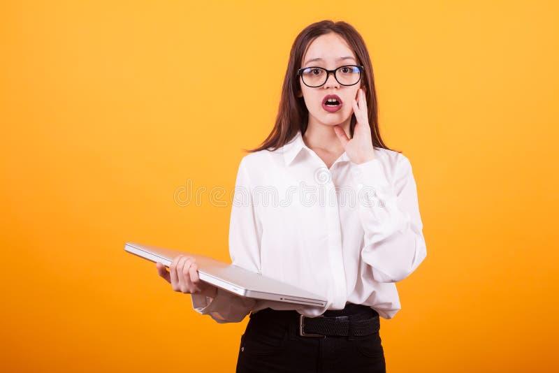 El retrato del adolescente sorprendido que mira la cámara con el ordenador portátil en su entrega el fondo amarillo imagen de archivo