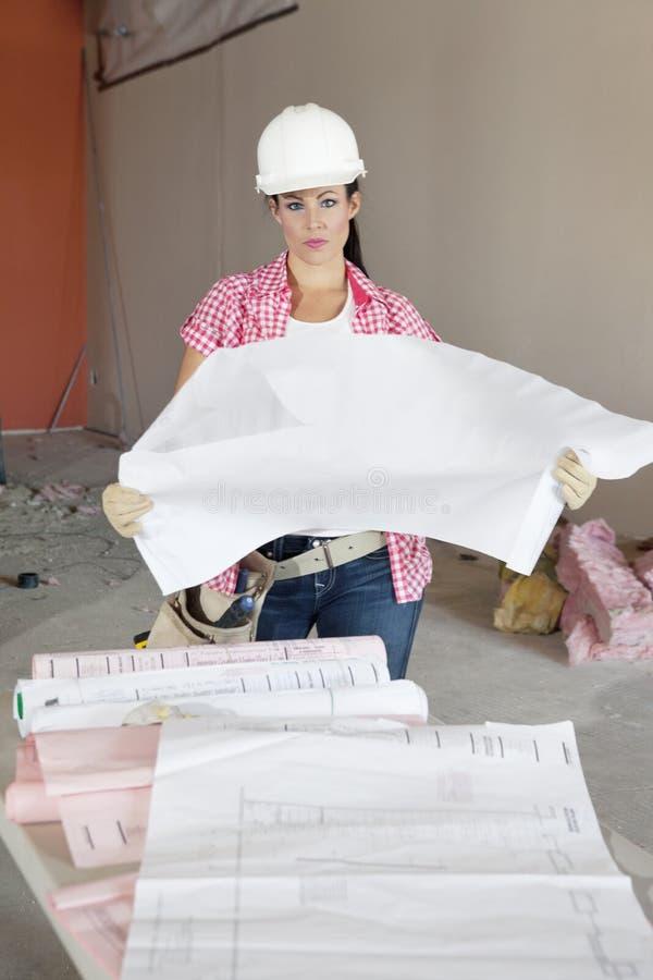 El retrato del arquitecto de sexo femenino serio que sostiene el edificio planea en el emplazamiento de la obra fotos de archivo