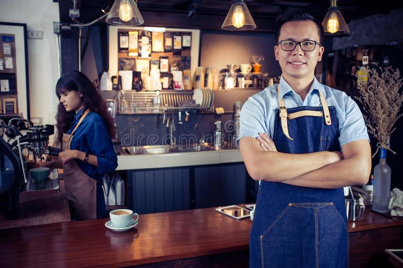El retrato del barista asiático con los brazos cruzó en el contador en café imagenes de archivo
