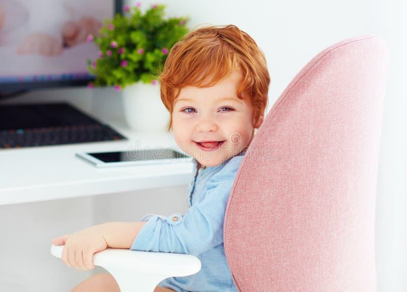 El retrato del bebé feliz del niño se está sentando en silla en el lugar de trabajo imagenes de archivo