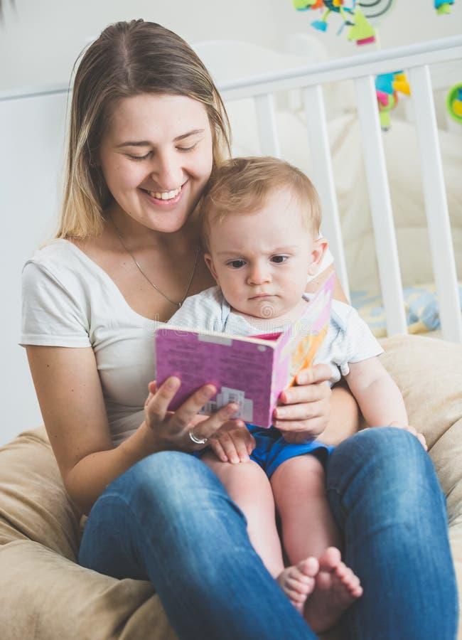 El retrato del bebé que se sienta en madres traslapa y el libro de lectura imagenes de archivo