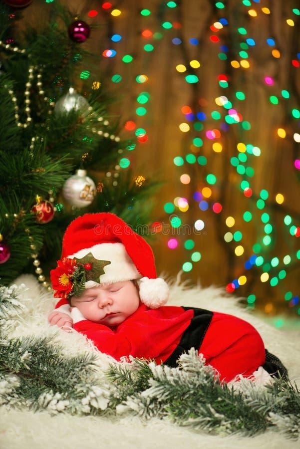 El retrato del bebé recién nacido en Papá Noel viste la mentira debajo del árbol de navidad imagen de archivo