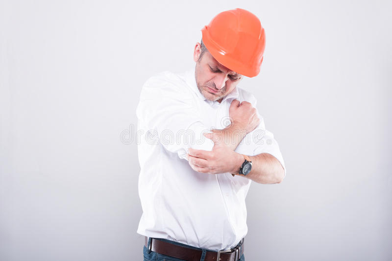 El retrato del casco de protección que lleva del contratista que sostiene el codo le gusta hurtin imagen de archivo libre de regalías