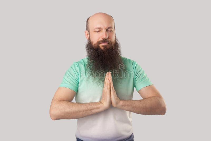 El retrato del centro serio tranquilo envejeció al hombre calvo con la barba larga en la situación verde clara con los ojos cerra foto de archivo libre de regalías