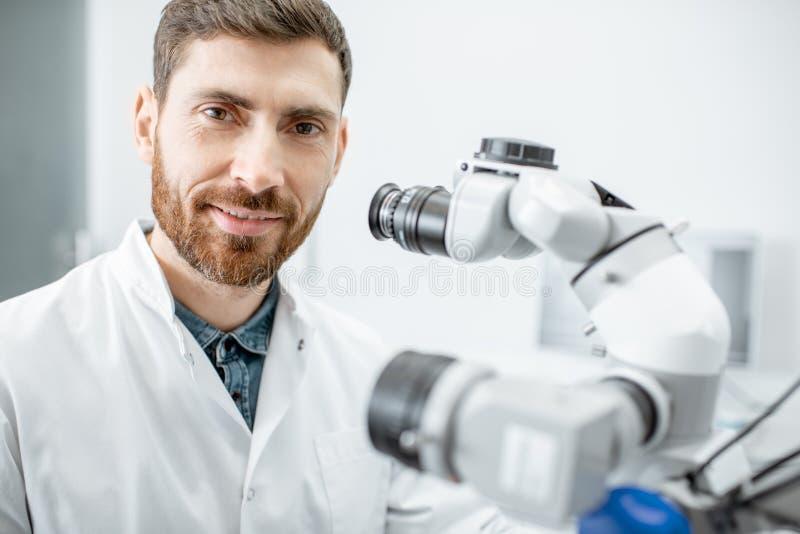 El retrato del dentista con un microscopio imágenes de archivo libres de regalías
