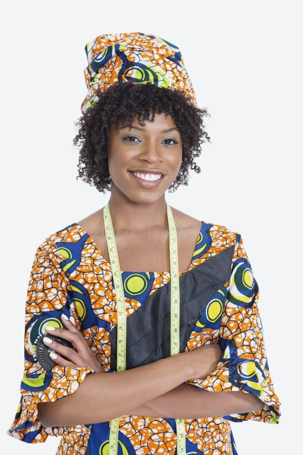 El retrato del diseñador de moda de sexo femenino joven en manos derechas del traje africano de la impresión plegó el fondo gris imagenes de archivo