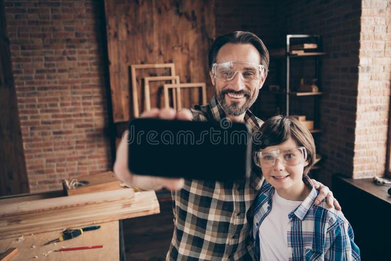 El retrato del dispositivo contento alegre positivo encantador lindo de la mano del control del niño del papá hace gafas de los v imagen de archivo libre de regalías
