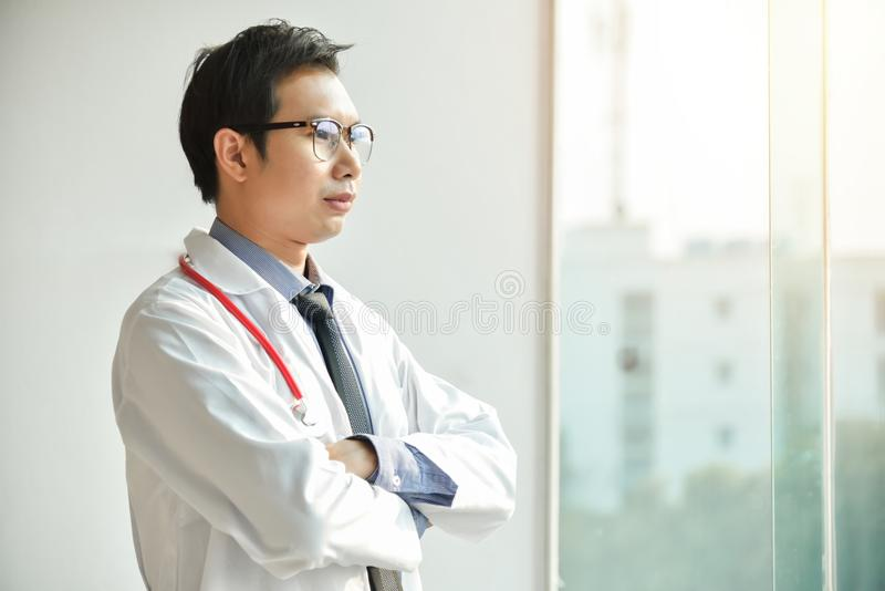 El retrato del doctor de sexo masculino asiático joven está presentando con los brazos cruzados foto de archivo libre de regalías
