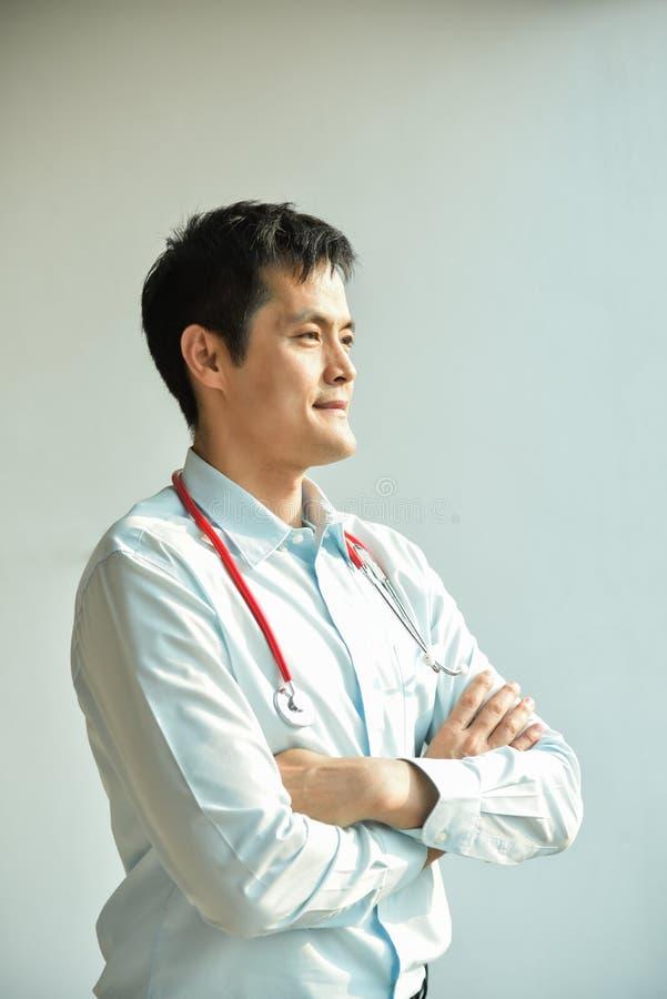 El retrato del doctor de sexo masculino asiático joven está sonriendo fotografía de archivo libre de regalías