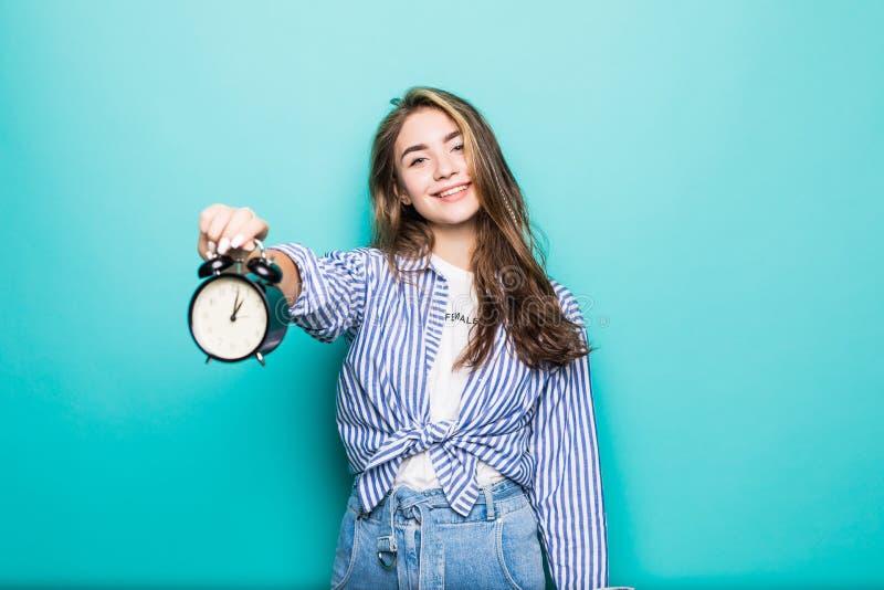 El retrato del estudiante de mujer desconcertado sonrisa joven en ropa del dril de algodón sostiene el despertador aislado en fon imagenes de archivo