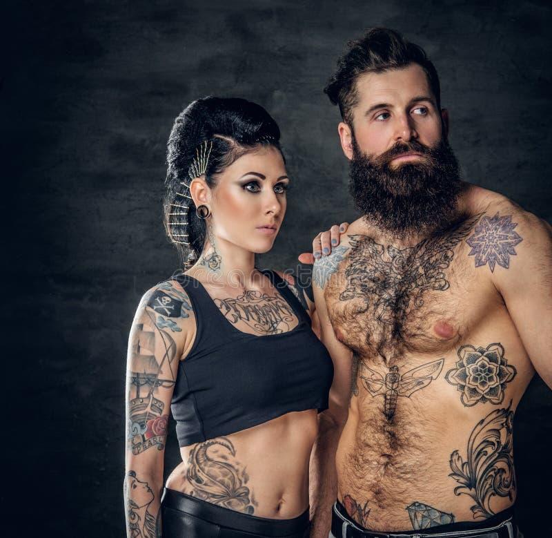 El retrato del estudio del cuerpo completo tatuó pares sobre fondo gris oscuro fotos de archivo