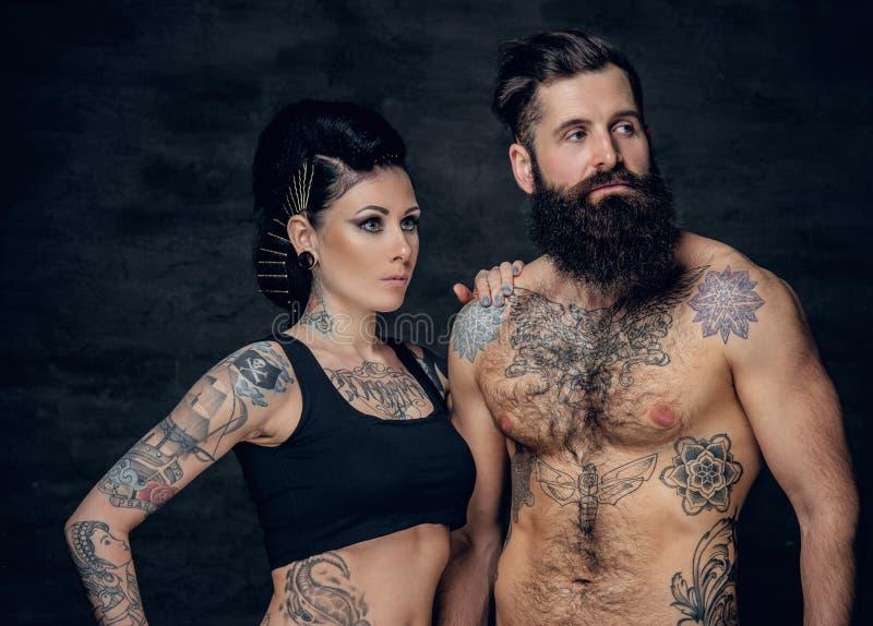 El retrato del estudio del cuerpo completo tatuó pares sobre fondo gris oscuro imagenes de archivo