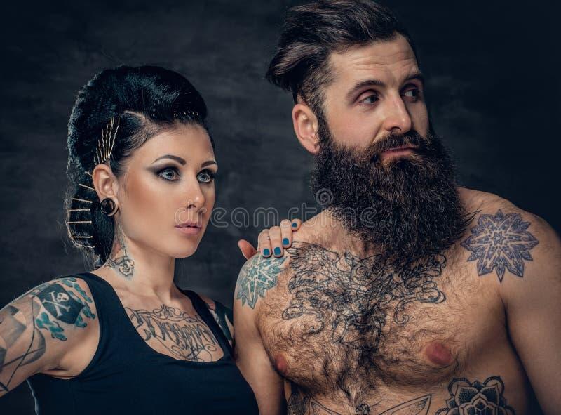 El retrato del estudio del cuerpo completo tatuó pares sobre fondo gris oscuro fotos de archivo libres de regalías