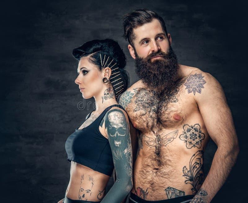 El retrato del estudio del cuerpo completo tatuó pares sobre fondo gris oscuro imagen de archivo