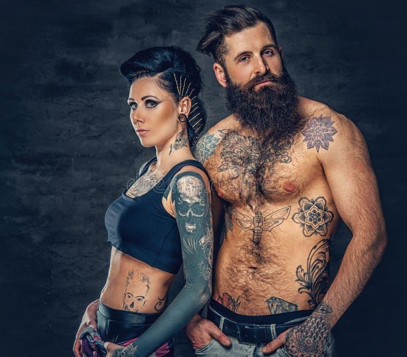 El retrato del estudio del cuerpo completo tatuó pares sobre fondo gris oscuro fotografía de archivo