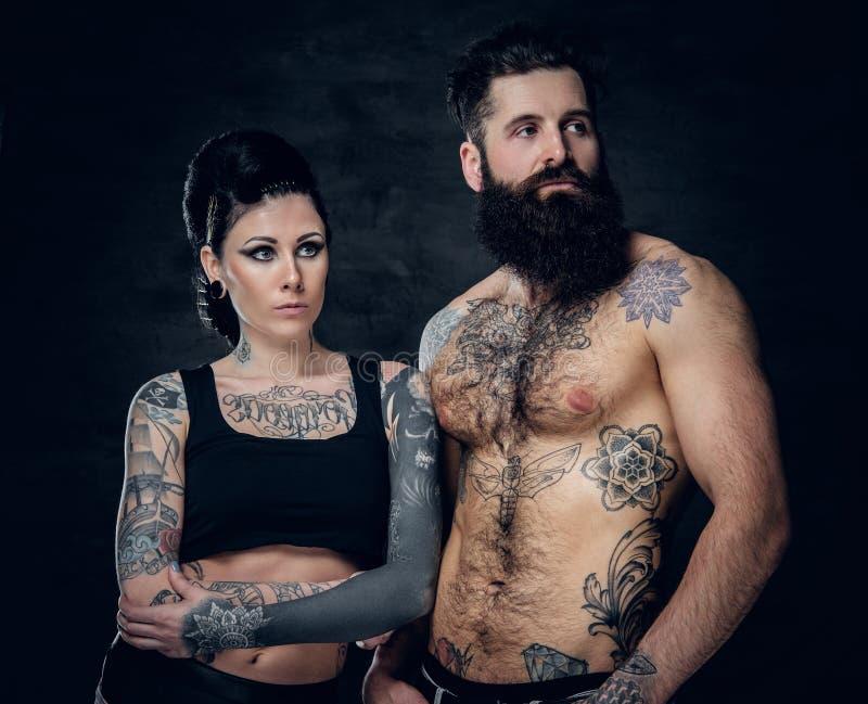 El retrato del estudio del cuerpo completo tatuó pares sobre fondo gris oscuro fotografía de archivo libre de regalías