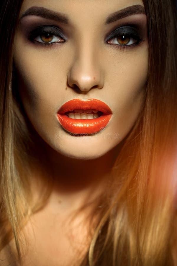 El retrato del estudio de la muchacha hermosa con compone la mirada de la cámara con la boca abierta imagen de archivo