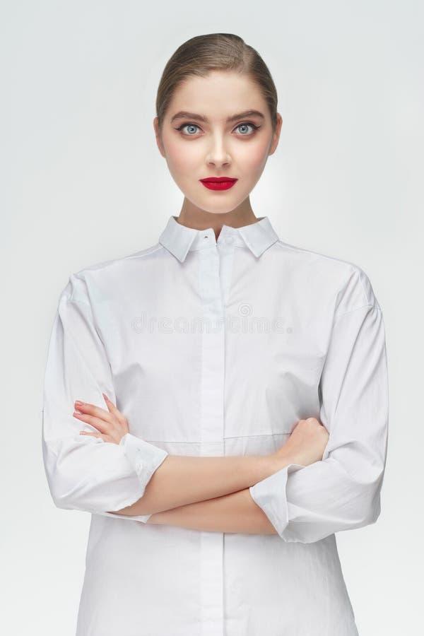 El retrato del estudio de la muchacha del negocio en la camisa blanca en gris aisló el fondo Concepto: un encargado o un estudian imagen de archivo libre de regalías
