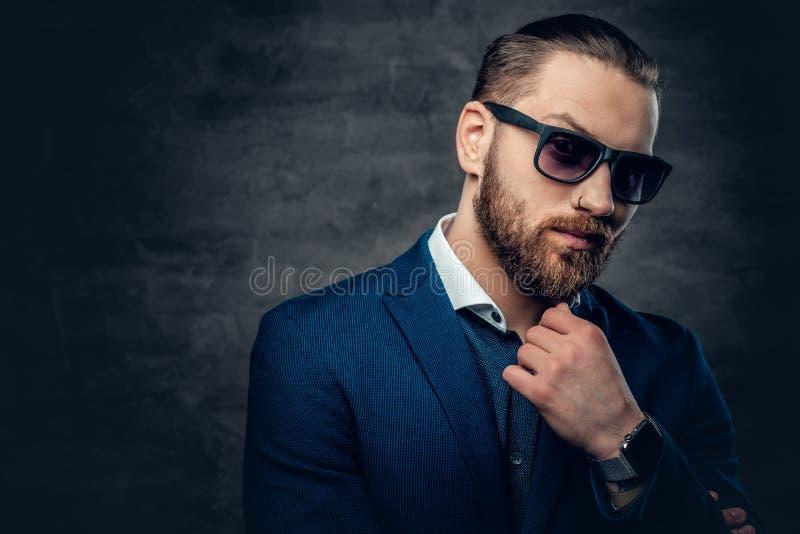 El retrato del estudio del varón barbudo se vistió en una chaqueta azul y gafas de sol foto de archivo