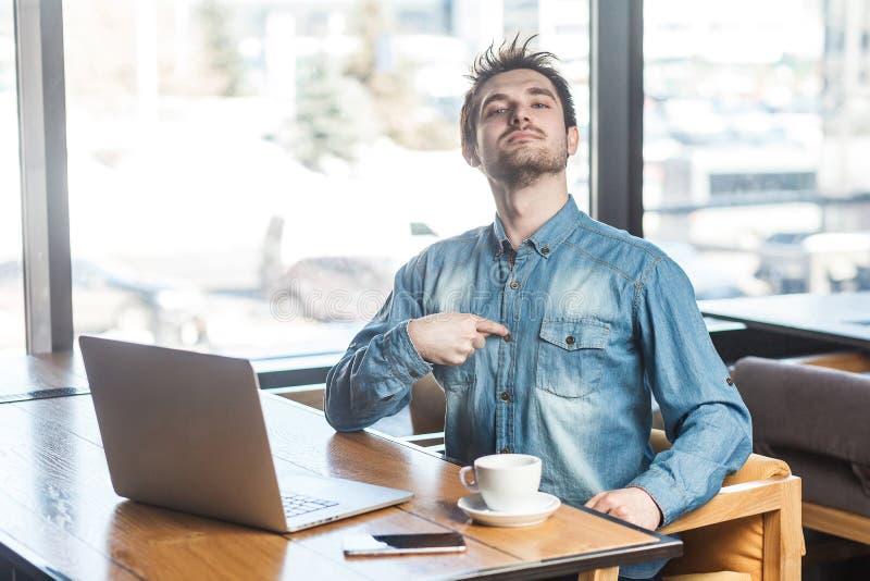 El retrato del freelancer joven barbudo egoísta satisfecho egoísta confiado en camisa de los tejanos se está sentando en el café, imagen de archivo