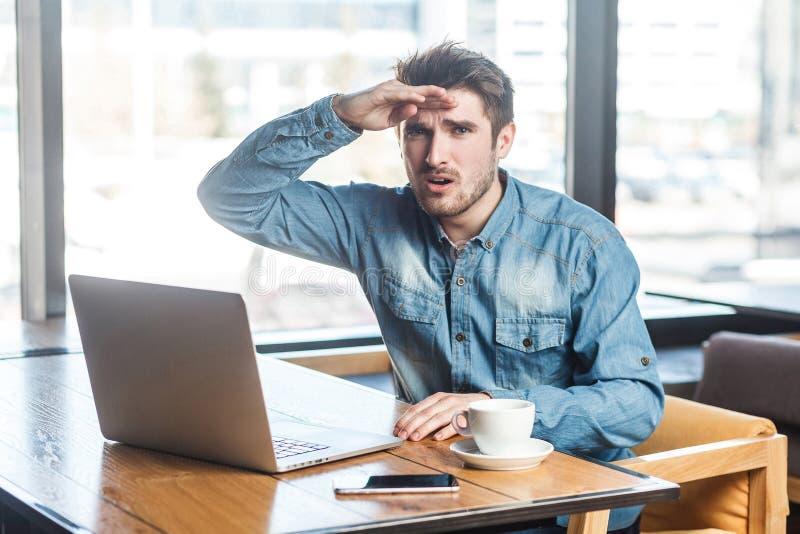 El retrato del freelancer joven barbudo hermoso preguntado en camisa de los tejanos se está sentando en café y está trabajando en imagen de archivo