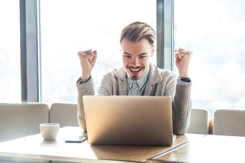 El retrato del freelancer joven barbudo positivo satisfecho sorprendente hermoso en chaqueta gris se está sentando en el café, mi imagen de archivo libre de regalías