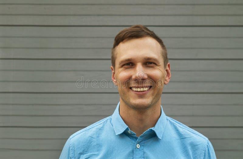 El retrato del freelancer joven está sonriendo en fondo gris fotografía de archivo