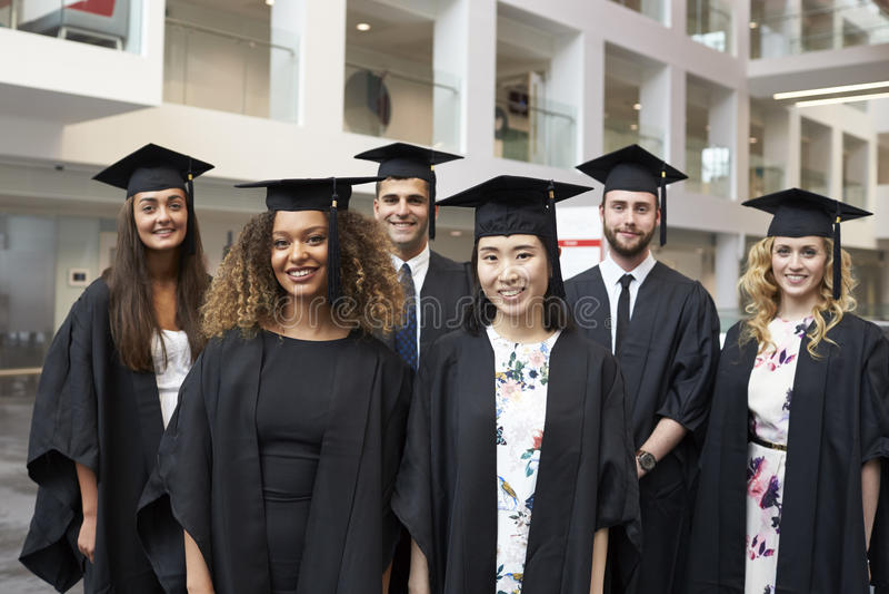 El retrato del grupo de la universidad gradúa en casquillo y vestido foto de archivo libre de regalías