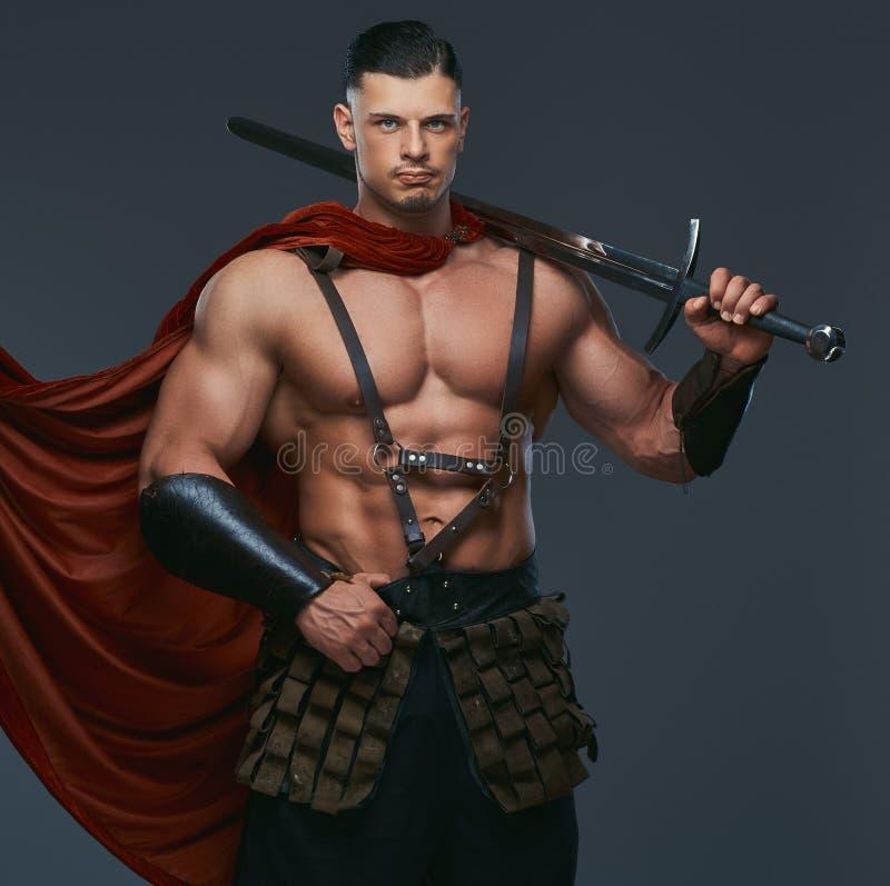 El retrato del guerrero de Grecia antigua con un cuerpo muscular se vistió en espada de los controles de los uniformes de la bata imagenes de archivo