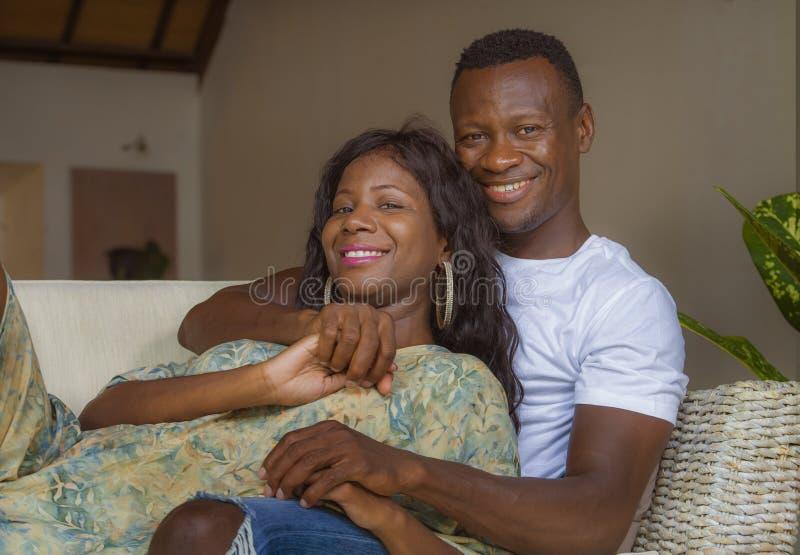 El retrato del hogar de la forma de vida de pares afroamericanos románticos felices y acertados jovenes en amor relajó sentarse c foto de archivo libre de regalías