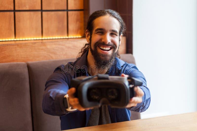 El retrato del hombre adulto joven barbudo feliz en el estilo sport que se sienta en café, llevando a cabo y mostrando el vr detr foto de archivo libre de regalías