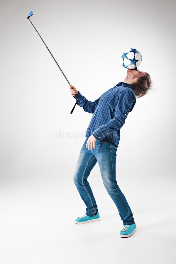 El retrato del hombre con la bola, sosteniendo el palillo del selfie en el fondo blanco foto de archivo libre de regalías