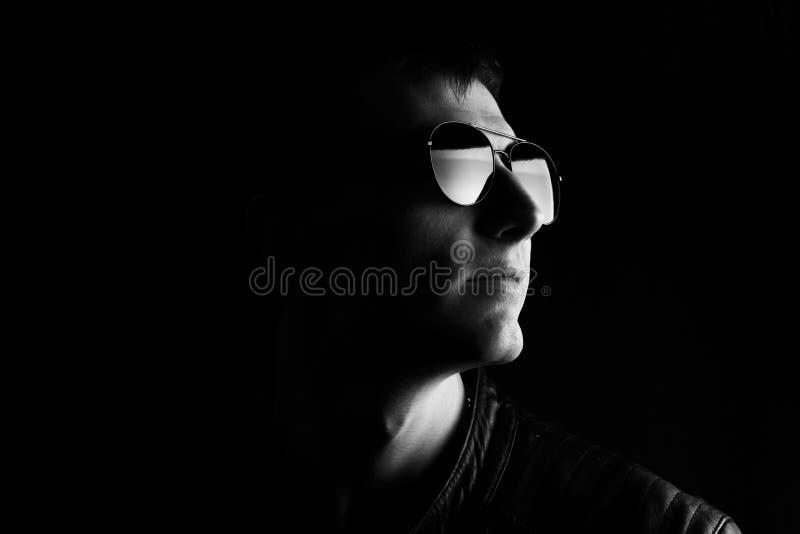 El retrato del hombre de j?venes Hombre joven del primer en una chaqueta de cuero negra y gafas de sol foto de archivo libre de regalías