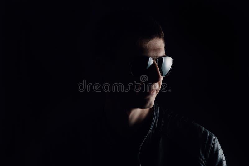 El retrato del hombre de j?venes Primer del hombre joven serio en una chaqueta de cuero negra y gafas de sol imagen de archivo