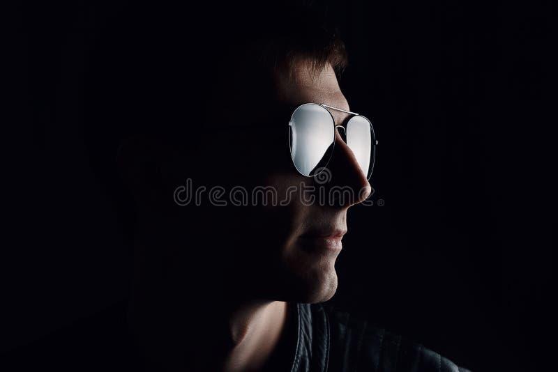 El retrato del hombre de j?venes Primer del hombre joven serio en una chaqueta de cuero negra y gafas de sol foto de archivo