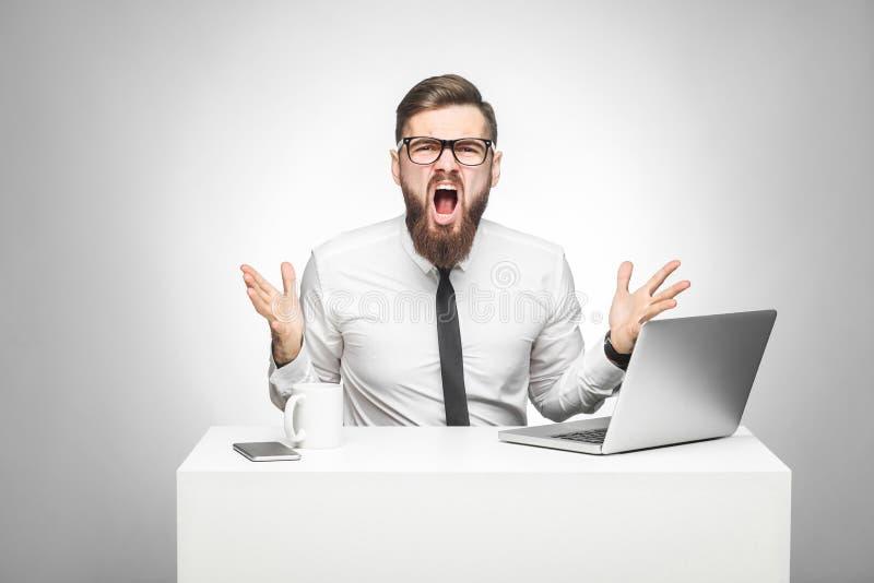 El retrato del hombre de negocios agresivo en la camisa blanca y el lazo negro se están sentando en oficina y están teniendo mal  imágenes de archivo libres de regalías