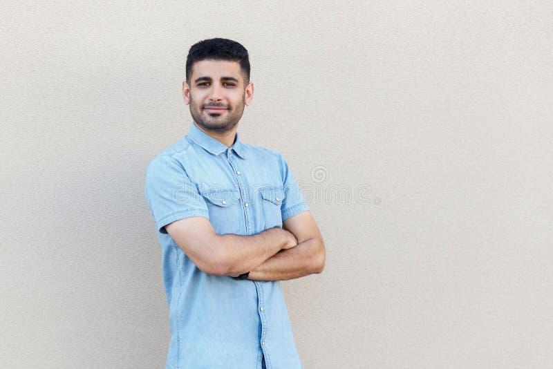El retrato del hombre de negocios barbudo joven hermoso acertado confiado en la situación azul de la camisa, cruzó los brazos y l foto de archivo libre de regalías